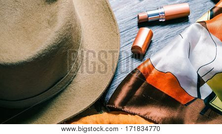 Set of female accessories in gold, tan and brown shades. Hat, lipstick and necktie