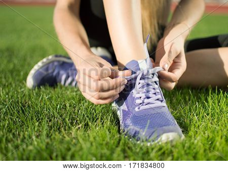 Active healthy lifestyle athlete woman tying shoelaces. Happy sporty woman runner shnunuruet her pink sneakers on a green lawn in the city park in preparation for fitness jogging.