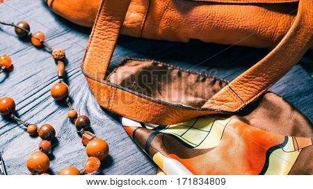 Fall set of womens accessories in gold, tan and brown shades. Leather handbag, beads and necktie