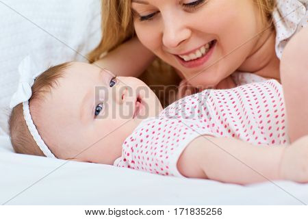 Mother playing with her baby on the bed. Mom smiles to her child.