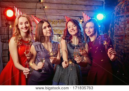 Girls for birthday party in the caps on their heads and with sparklers their hands.