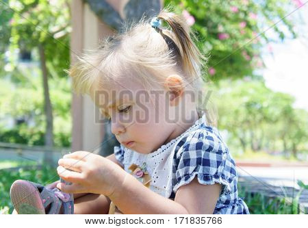 Cute Little Girl With Straight Face In Summer Day. Mending Sandals.