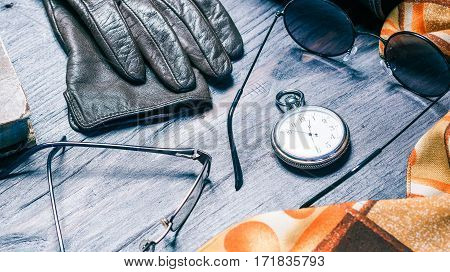 Female accessories for sunny and cool weather. Sunglasses, leather gloves, pocket watch and necktie