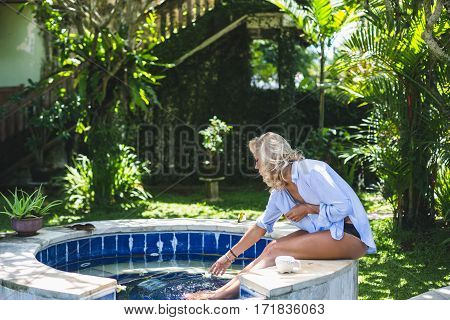Young beautiful blonde woman sitting at the edge of swimming pool in the garden