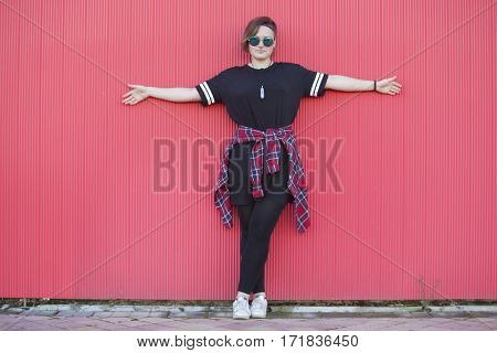 teen androgynous woman with hipster glasses on a pink background