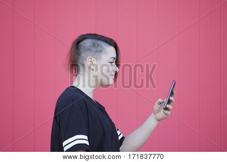 Teen androgynous woman connecting to internet isolated on a pink background