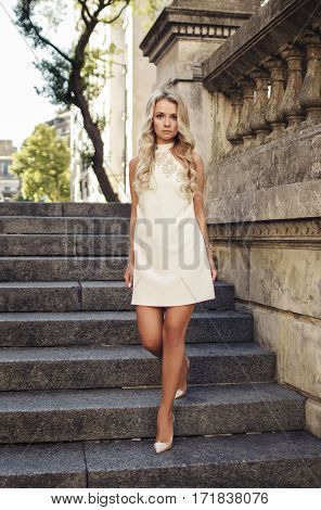 Attractive blonde girl in white dress going down stairs outdoors in beautiful old city.