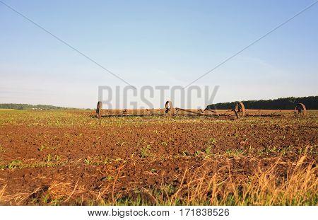 old metal plow lying on a plowed field in the village