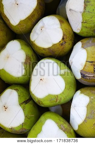 Whole coconuts in pile - closeup photo