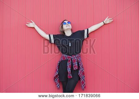 cheerful androgynous woman with hipster glasses on a pink background