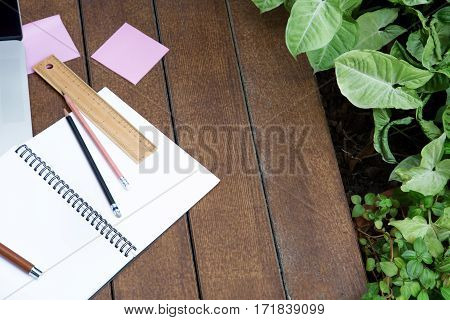 Workspace relaxing chill out work for office and design empty notebok note pen pencil ruler stationary on wood floor with plant