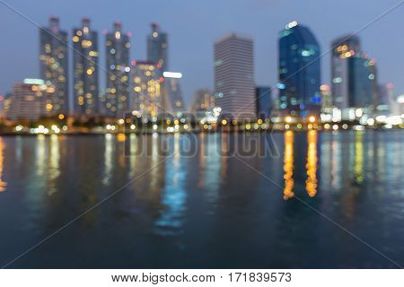 Twilight blurred bokeh office building with water reflection in public park abstract background