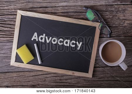 Advocacy On Blackboard With Cup Of Coffee, With Glasses On Wooden Background.