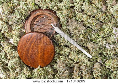 Wood grinder and spliff with dry cannabis buds background