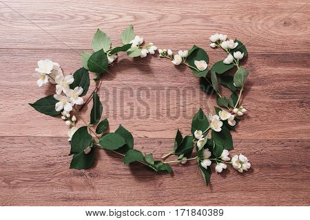 Frame of jasmine flowers and petals on the wooden background. Greeting card. Conceptual photography. Wedding invitation card. Valentine day. Flat lay top view copyspace.