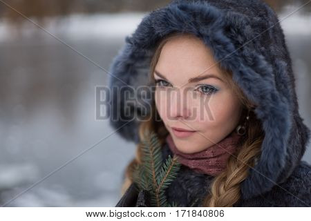 woman in a blue winter fur coat standing on the street in full growth