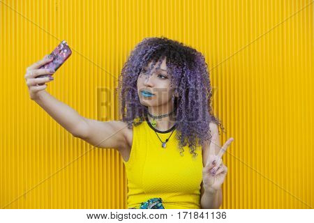 Young woman with afro hair taking a picture of herself  isolated on yellow background