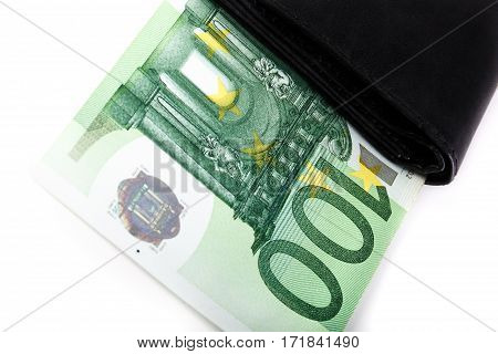 Banknotes of hundred euros sticking out of black wallet closed on white background. Money in cash. Closeup image.