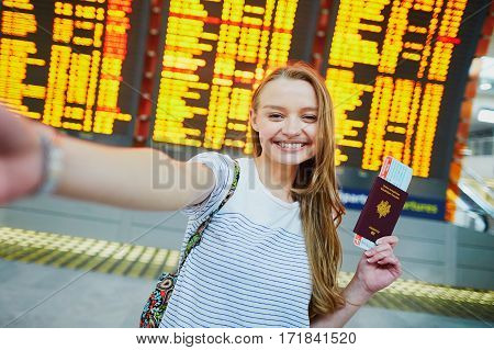 Girl In International Airport, Taking Funny Selfie With Passport And Boarding Pass Near Flight Infor