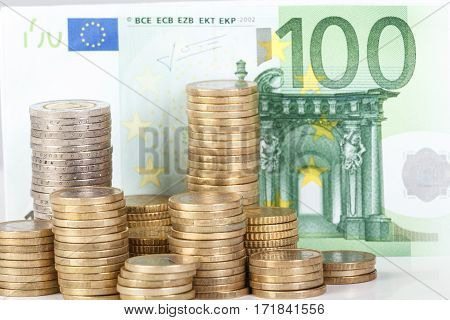 Euro Coins Stacked On Euro Banknotes Background.