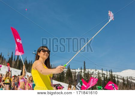 Sheregesh Kemerovo region Russia - April 16 2016: Grelka Fest is a sports and entertainment activity for ski and snowboard riders in bikini in Russia Sheregesh. Woman makes selfie with mobile phone on the selfie stick.