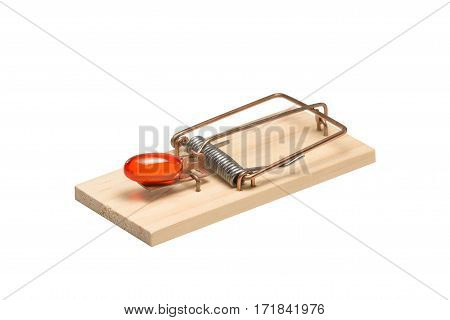 Orange gelatin capsule or pill as bait in a mousetrap. Studio close-up isolated on white. Concepts could include addiction desire danger risk others.