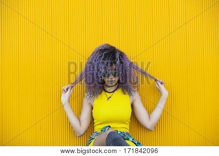 teen woman with purple afro hair and colorful galsses on a yellow background