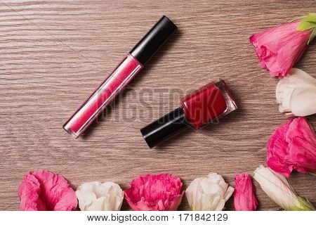 Red and white flowers lie on the wooden background. Space for text and design. Female nail polish and lip gloss. Natural cosmetic. Personal care