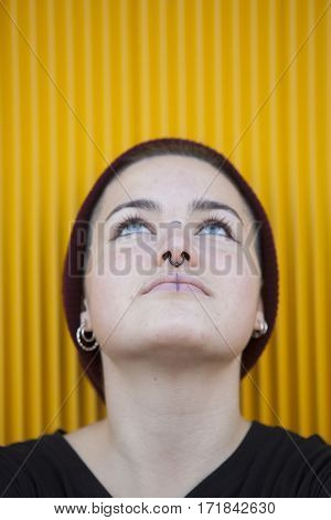 portrait of a thoughtful teen gay woman with a piercing on her nose solated on yellow background