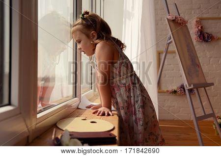 Little girl in nice dress looking into a window