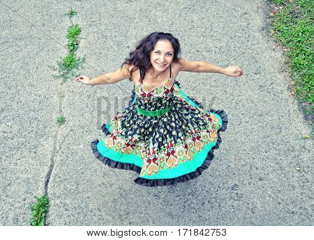 Happy Woman Spinning In A Dress On A Summer Day Outdoors