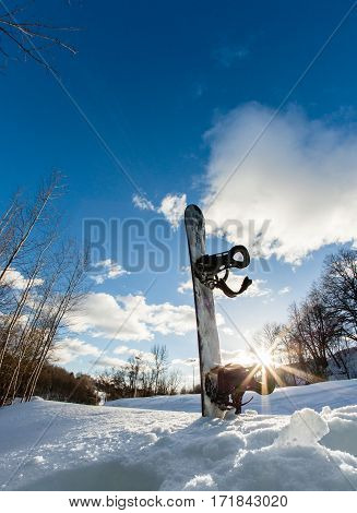 Ski slope, snowboard and blue cloudy sky