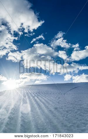 Unbroken ski slope and blue cloudy sky