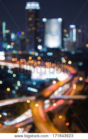 Night blurred bokeh light highway interchanged and office building abstract background