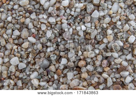 Naturally rounded gravel at sea shore, nature background texture pattern