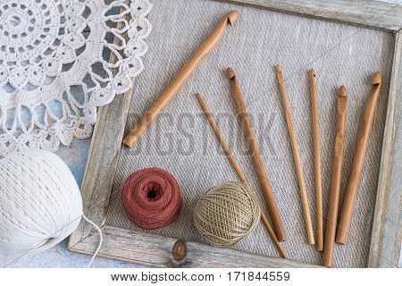 The composition on the theme of knitting. A set of hooks of different sizes and balls of cotton yarn in old wooden frame, near openwork doily.