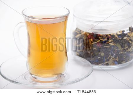 Picking of green tea with herbs and berries in a jar of glass and a cup of tea