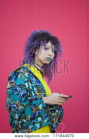 portrait of a teen woman listening to music from her phone on a pink wall