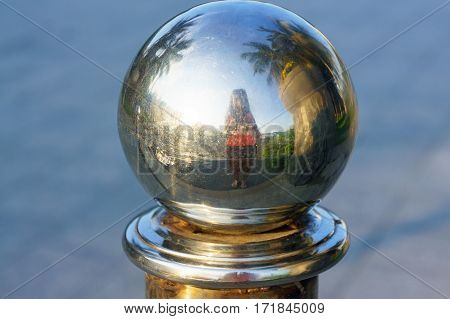 Reflection Of Girl With Camera In Round Metal Bowl. Fence. Scenery.