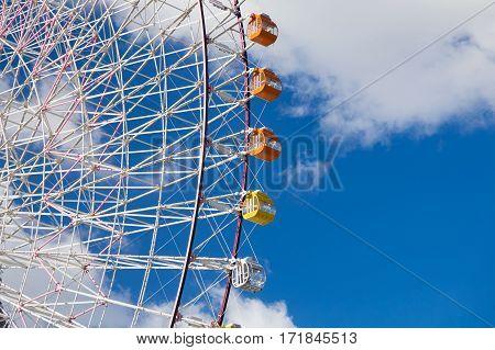 Ferris wheel in amusement Park againts blue sky background