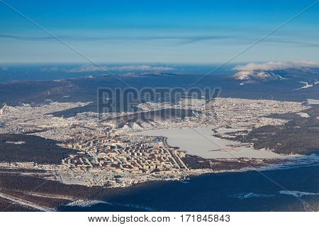 View from above of the industrial center of the Urals city of Zlatoust in winter, surrounded by winter mountains.