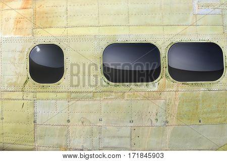 riveted khaki fuselage with portholes of light aircraft closeup