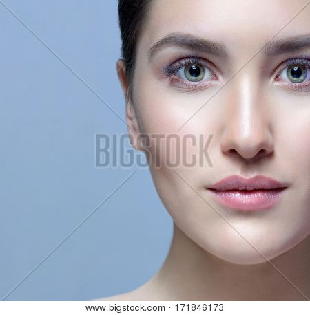 closeup portrait of attractive young caucasian woman brunette  on blue background studio shot lips face  head and shoulders perfect skin care