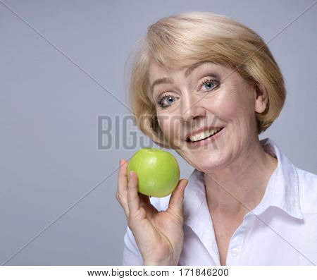 Beautiful Matured Woman happy cheerful caucasian with green apply toothy smile blond studio shot. Grey background.Copy space. Dental. Perfect white teeth. Healthy eating concept. Raw vegetarian fruit