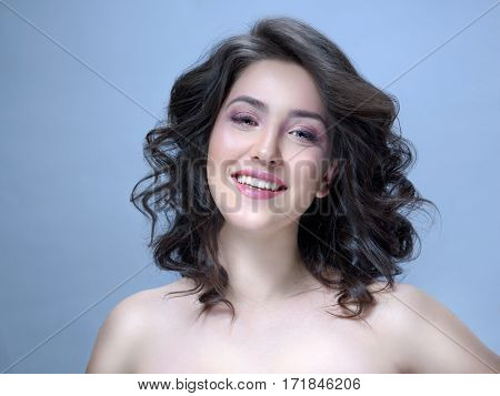 Beauty Spa Woman with Perfect skin Portrait. Beautiful Brunette curly Hair. Young Caucasian with Fresh looking Skin. Beauty Woman Face . Blue background. Studio shot. Happy Cheerful Toothy Smiling