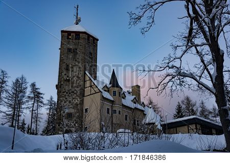 The observation tower in Liberec. The old bricky tower with new building. Winter time. Cold sunny day. The evening view of the building, trees, snow and clear blue sky.