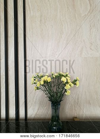 Vase of yellow carnation flower in the center of marble bar in the hotel lobby with blur background for decoration