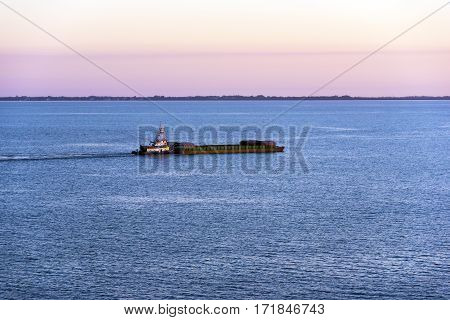 Tugboat pushing a barge across tampa bay at sunset