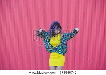 yellow blue and pink photo of a teen woman with afro hair listening and dancing to the music