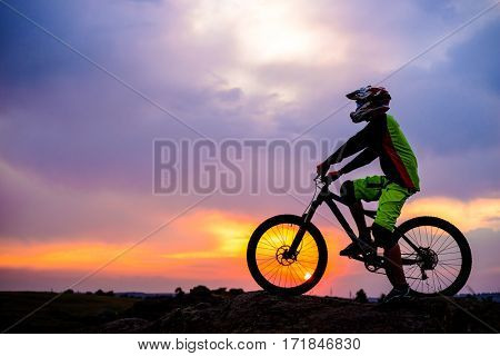 Professional Down Hill Cyclist Resting with Bike on the Rock at Sunset. Extreme Sport Concept.